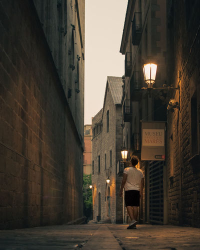 HUAWEI Photo Award: After Dark Adult Alley Architecture Building Building Exterior Built Structure City Direction Full Length Illuminated Lifestyles Men One Person Outdoors Real People Rear View Residential District Standing Street Walking