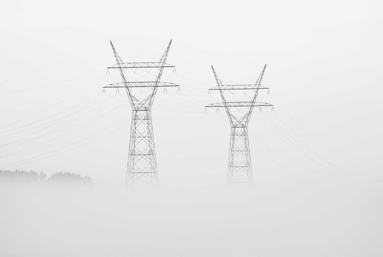 Electricity pylons on land against clear sky during foggy weather