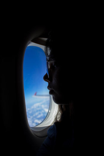 Portrait of man looking through airplane window