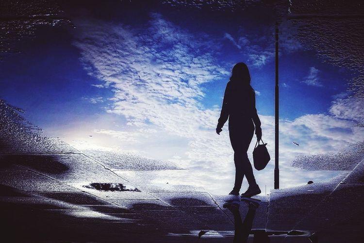 Silhouette woman walking on beach against sky