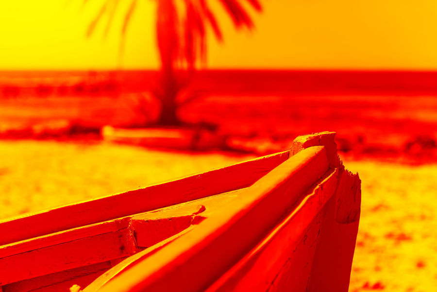 Front of a blue wooden boat on a sandy beach by the sea Beach Close-up Focus On Foreground Holiday Horizon Land Nature No People Orange Color Outdoors Red Sand Sea Sky Sunset Trip Vacations Water Yellow