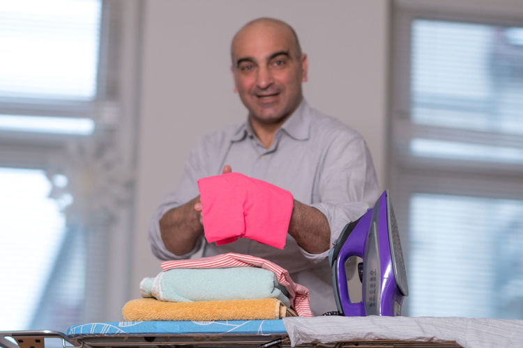 Portrait Of Man Holding Cloth At Home