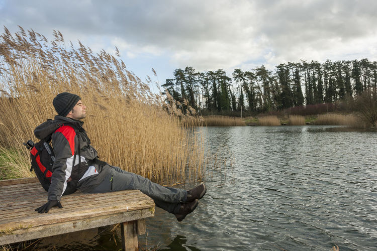 Young adult relaxing in nature One Person Water Leisure Activity Cloud - Sky Real People Lake Beauty In Nature Sky Lifestyles Full Length Sitting Nature Non-urban Scene Young Adult Day Young Men Scenics - Nature Clothing Warm Clothing Outdoors
