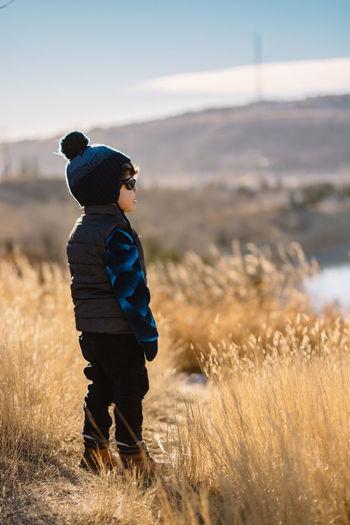 Boy in warm clothing on field
