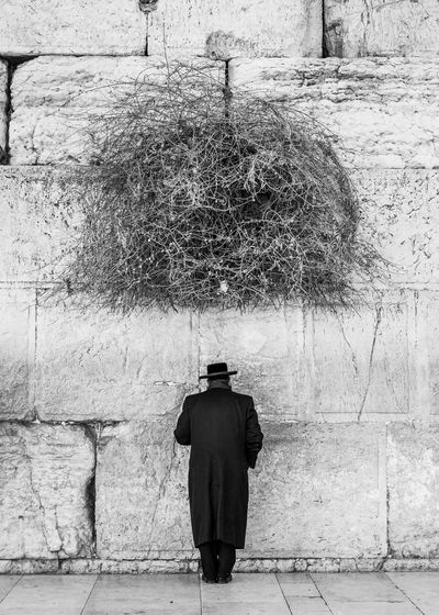 Rear view of a man standing against wall