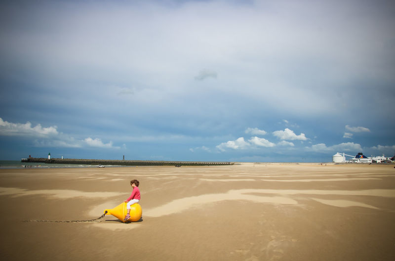 Child sitting on beach against sky