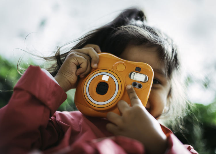 Close-up portrait of woman holding camera