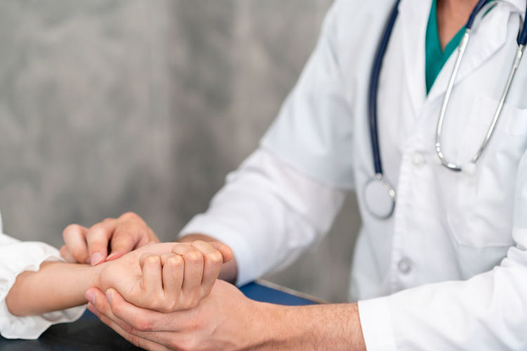 Midsection of doctor taking pulse of patient at clinic