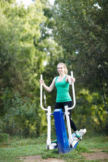 Happy young woman exercising on cross trainer in park