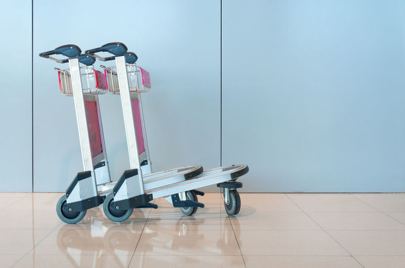 Close-Up Of Luggage Cart On Tiled Floor Against Wall