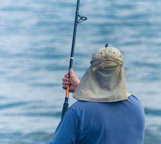 Blue Fisherman Casual Clothing Day Fisherman Fishing Fishing Pole Focus On Foreground Hat Having Fun Leisure Activity Lifestyles Nature Nature Nikonphotography Ocean Outdoors Part Of Person Recreational Pursuit Relax Relaxing Moments Rippled Tourism Vacation View From Behind Water
