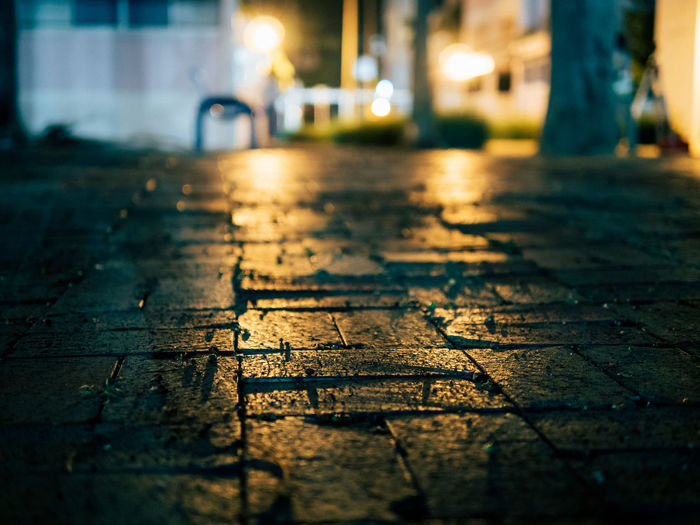 Neighbourhood street at dusk Bokeh City Street Close-up Depth Of Field Dof Dusk Floor Focus On Foreground Ground Ground Level View Low Angle View Low Key Neighborhood Night Night Lights Nightphotography Outdoors Selective Focus Street Suburbia Surface Level Tiles