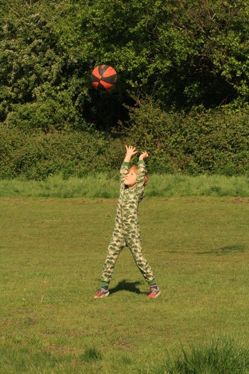 Boy playing with ball on grassy field