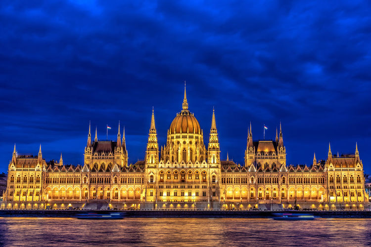 Illuminated hungarian parliament building by danube river in city at dusk