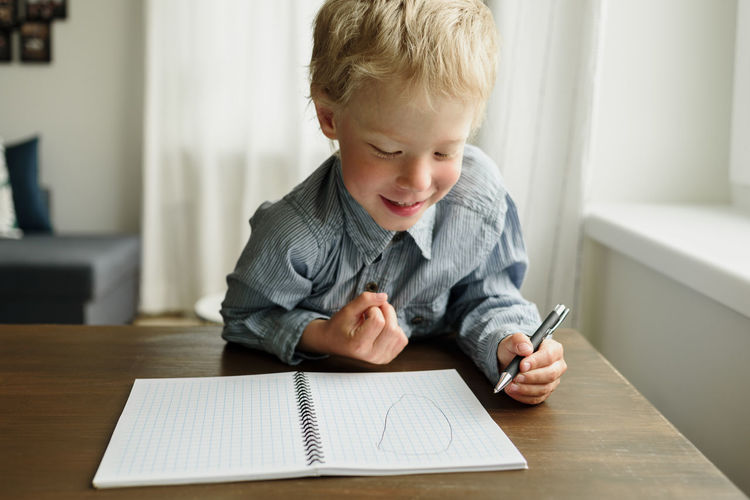 Close-up of smiling boy drawing in book on table at home