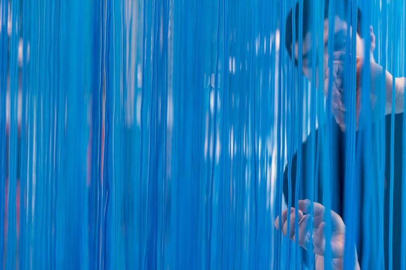 Man seen through blue strings