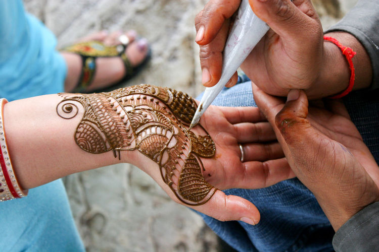 Cropped Image Of Man Making Henna Tattoo On Woman Hand