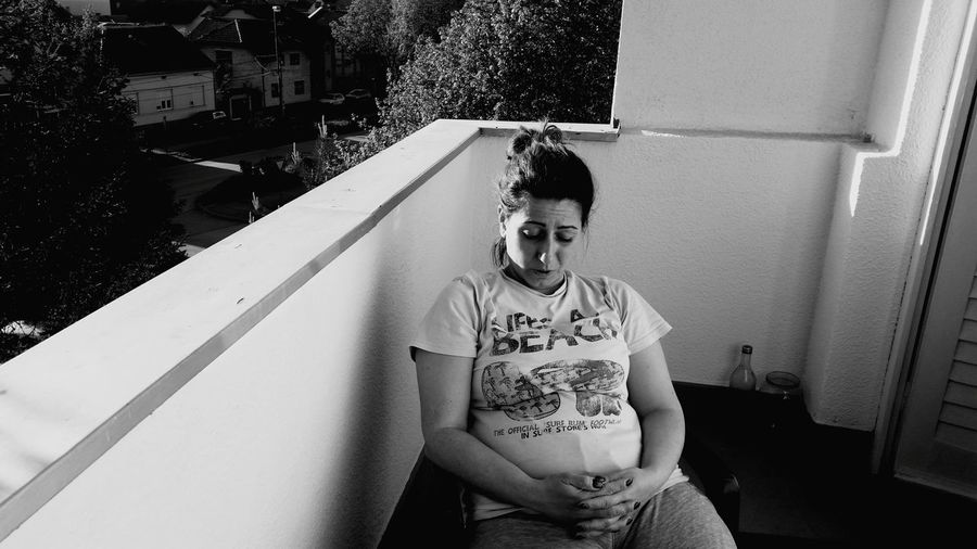 Pregnant woman sitting in balcony