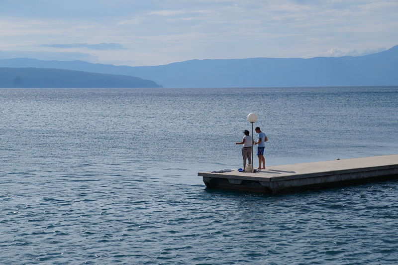 People Standing On Pier Amidst Sea Against Sky