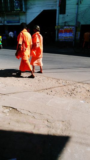 Two Monks Walking Parralaly On Road