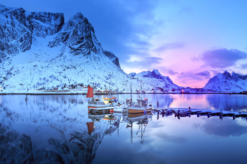 The fishermans village Reine on Lofoten Islands by night, Norway Barents Sea, Lofoten Islands, Northern, Reine, Town, Arctic, Atlantic, Coast, Cold, Europe, Fishing, Fjord, Harbor, Holiday, Ice, Landscape, Mountains, Nature, Night, Nordic, Nordland, North, North Sea, Norway, Norwegian, Ocean, Outdoor, Outdoors, Polar C Beauty In Nature Blue Day Iceberg Idyllic Mode Of Transport Moored Mountain Mountain Range Nature Nautical Vessel No People Outdoors Reflection Scenics Sea Sky Snow Sunset Tranquil Scene Tranquility Transportation Water Waterfront Winter