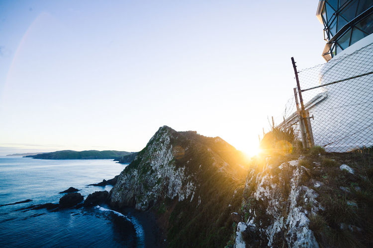 Lighthouse Beauty In Nature Clear Sky Copy Space Day Idyllic Lens Flare Mountain Nature Outdoors Scenics - Nature Sea Sky Sport Sun Sunlight Sunset Tranquil Scene Tranquility Water