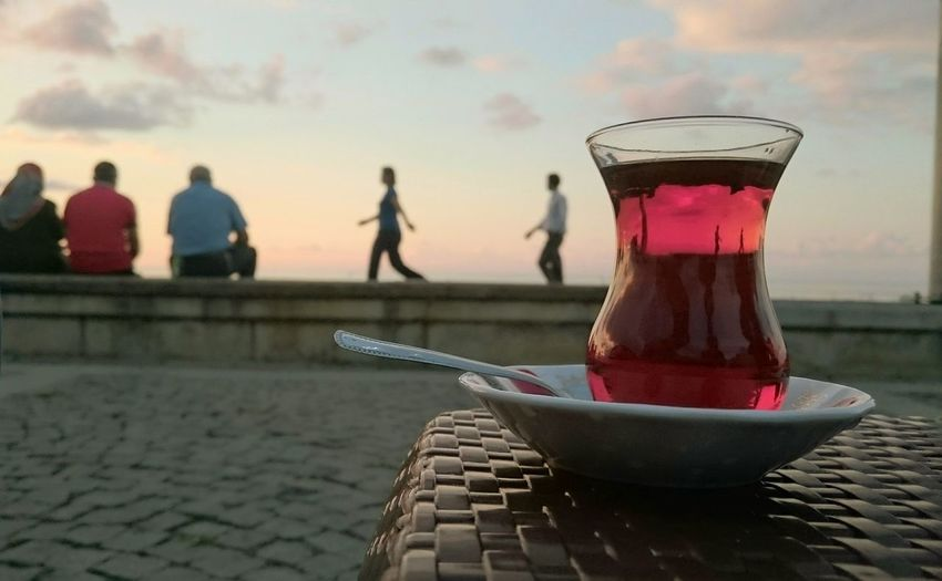 Drink on table against sky during sunset