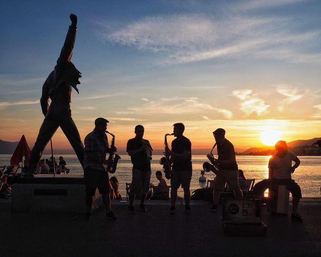 View of men on bridge against sky during sunset
