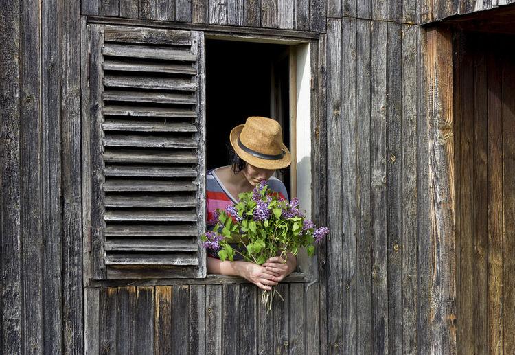 Woman sitting on wooden window