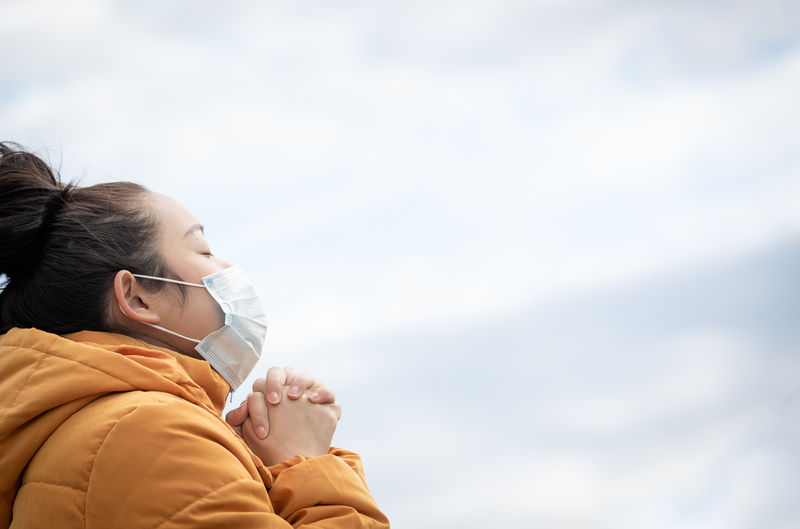 Close-up of woman wearing mask praying against sky