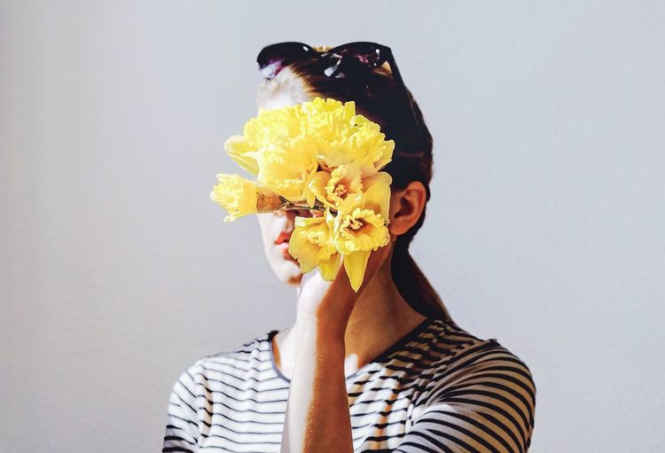 Woman Holding Yellow Daffodils Against White Background