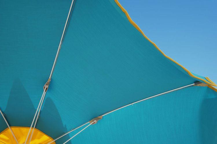 Low angle view of beach umbrella against blue sky