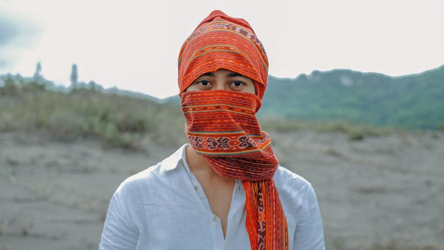 Portrait of man wearing scarf standing on field against sky