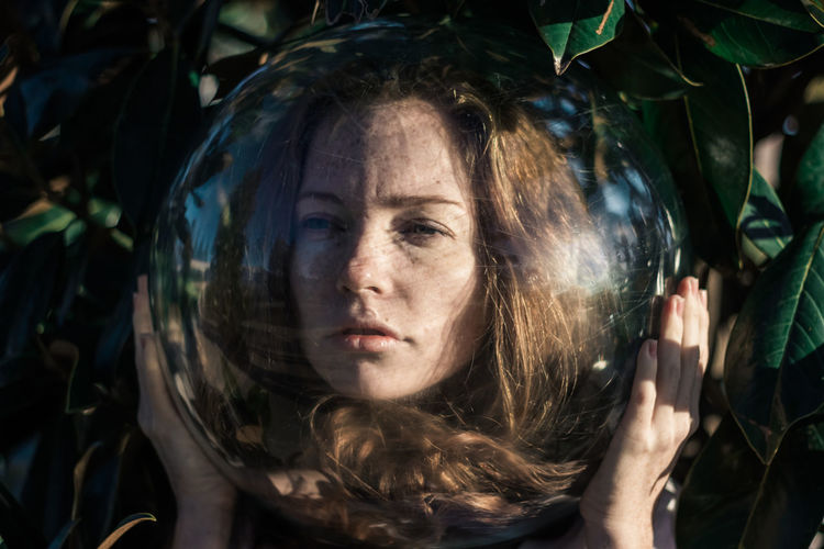 Close-up of young woman wearing glass ball on head against leaves