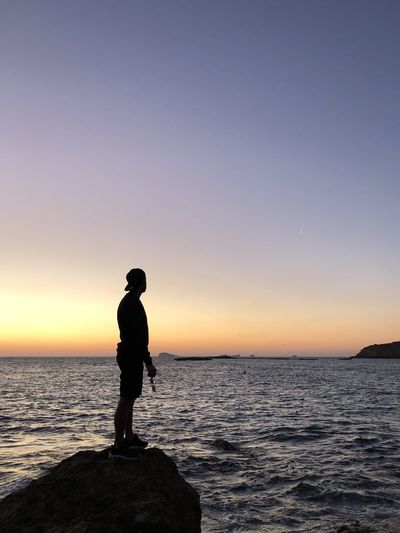 Silhouette man standing on rock against sea during sunset