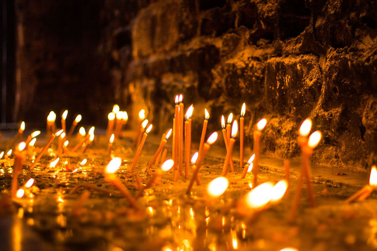 Close-up of burning candles by wall at night