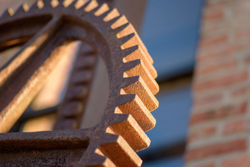 macro closeup of a rusty steel gear outside industrial factory in sunlight Antique Industrial Low Angle View Machinery Retro Rust Sunlight Wheel Clear Sky Close-up Day Factory Gear Machine Part Metal No People Outdoors Pattern Pitted Rusted Rusty Sprocket Steel Teeth Vintage