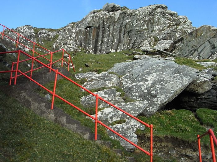Low angle view of steps by rock formations against clear sky