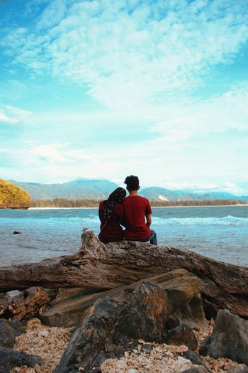 Rear View Of Couple Sitting On Driftwood At Beach