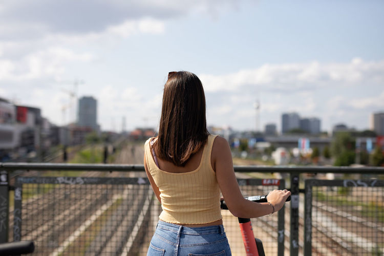 Rear view of woman standing by railing against sky