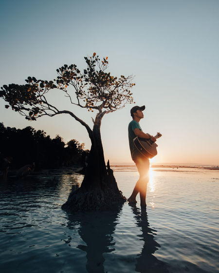 Full length of man playing guitar standing against sea and sky