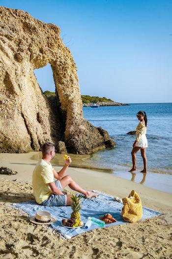 Men sitting on rock at beach against sky