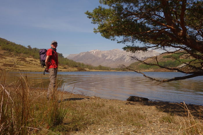 Beauty In Nature Casual Clothing Day Full Length Grass Landscape Leisure Activity Lifestyles Men Mountain Nature One Person Outdoors People Real People Scenics Sky Standing Torridon Mountains Tree Water Young Adult