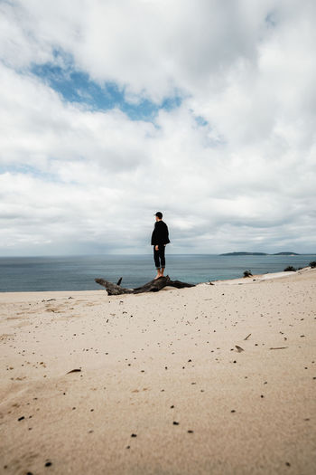 Man standing on driftwood at beach against sky