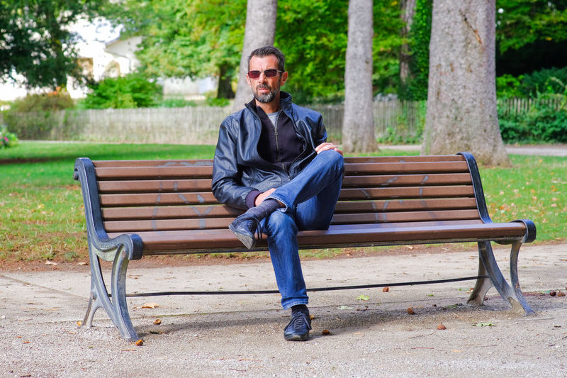 Full length of man sitting on bench outdoors