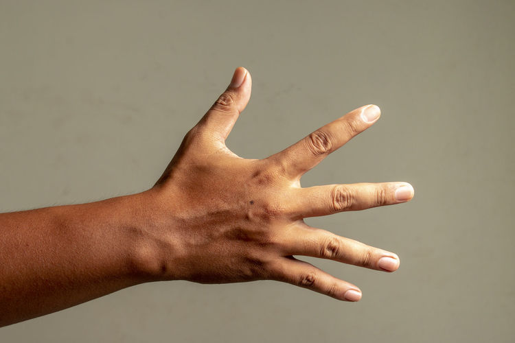 Close-up of hand against gray background
