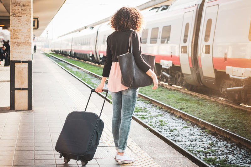 Casual Clothing Full Length Hair Hairstyle Journey Mode Of Transportation One Person Public Transportation Rail Transportation Railroad Station Railroad Station Platform Railroad Track Real People Rear View Track Train Train - Vehicle Transportation Travel Waiting Young Adult Young Women