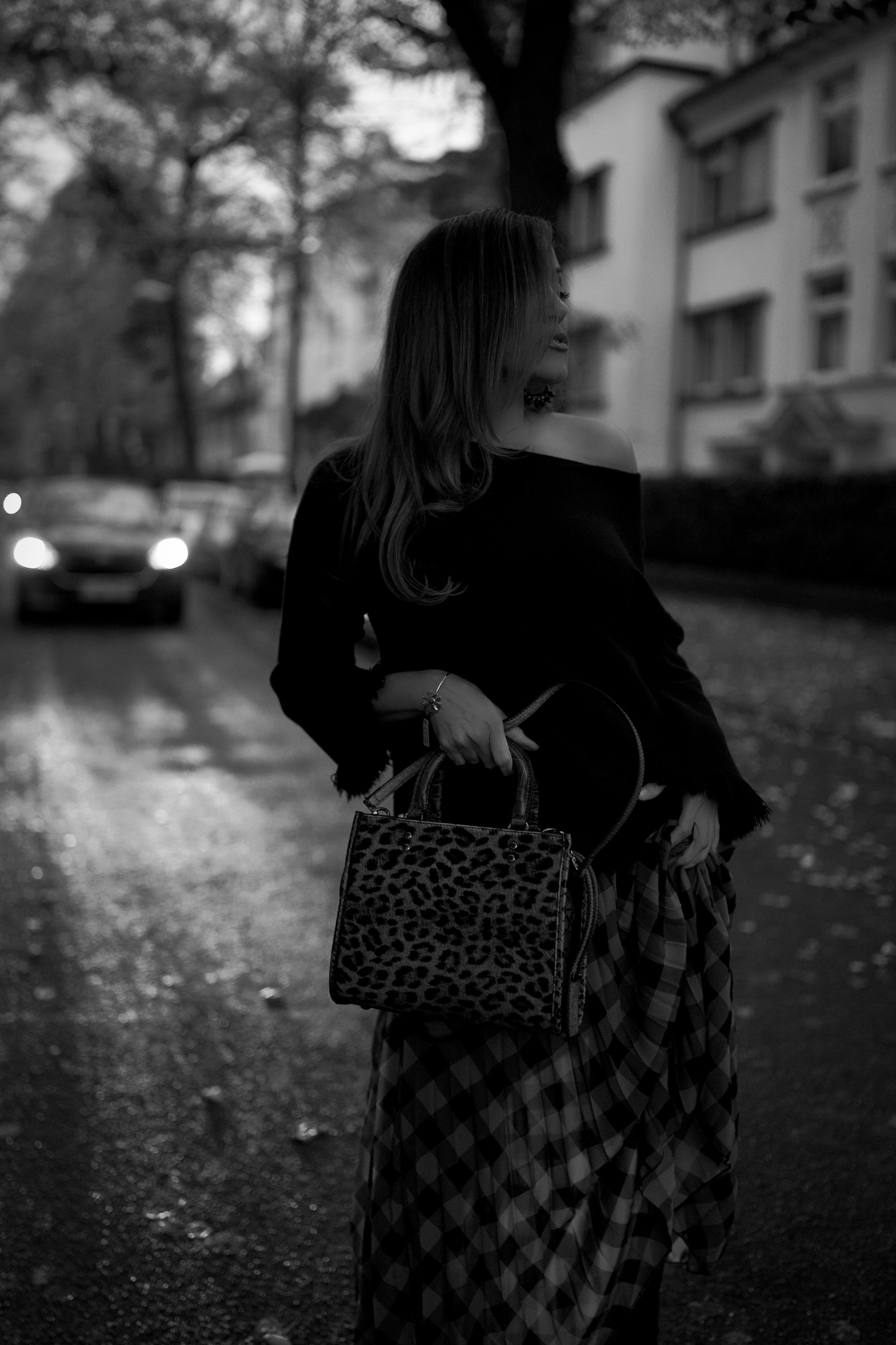 black, one person, white, black and white, women, monochrome, adult, monochrome photography, snapshot, darkness, city, street, focus on foreground, dress, architecture, car, young adult, lifestyles, standing, clothing, transportation, three quarter length, casual clothing, person, tree, nature, outdoors, mode of transportation, motor vehicle, female, leisure activity, road, day, built structure, rear view, vehicle, emotion, full length, hairstyle, building exterior, bag, plant, looking