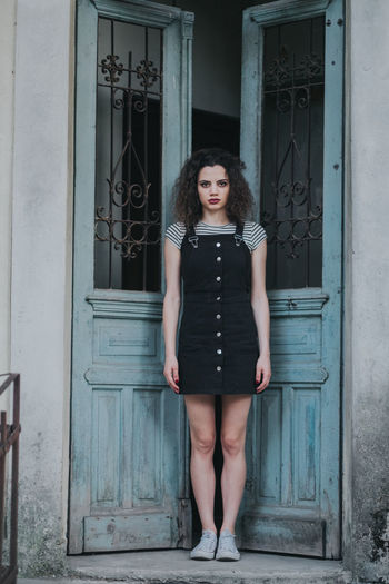 Portrait of young woman standing by door
