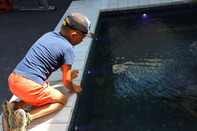 Side view of boy kneeling on poolside